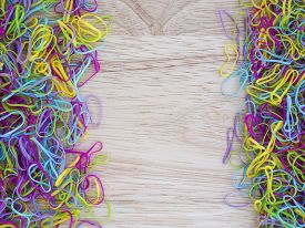 picture of rubber band  - Colorful rubber bands are on brown wood background - JPG