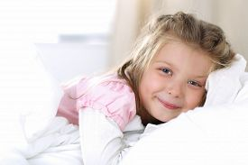 picture of sweet dreams  - Little girl wake up early morning after sleeping and lying in her bed - JPG