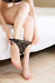 stock photo of tanga  - On the bed taking off her panties