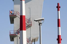 image of safety barrier  - Security camera barriers and a worker (out of focus) on top of the tower of the storm surge barrier in Krimpen aan den IJssel the Netherlands The storm surge barrier was the first installation (completed in 1958) of the Delta Works in the Netherlands. - JPG