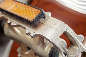 picture of pedal  - Part of a bicycle detail of a pedal bright orange part called cat eye - JPG