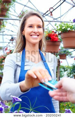 Young smiling seller florist working in flower shop.