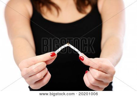 A picture of a young woman holding a cigarette and breaking it in the sign of stopping the addiction