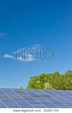 Photovoltaic panels in a solar power plant over a deep blue sky.