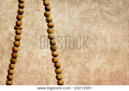 simple illustration featuring a close-up of prayer beads against simple light brown background