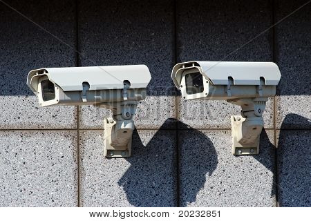 Two White Security Cameras On The Concrete Wall
