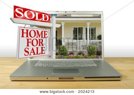 Sold Home For Sale Sign & New Home On Laptop