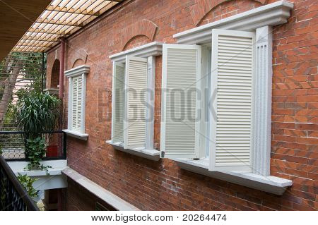 Several old style white wooden shutters in a villa
