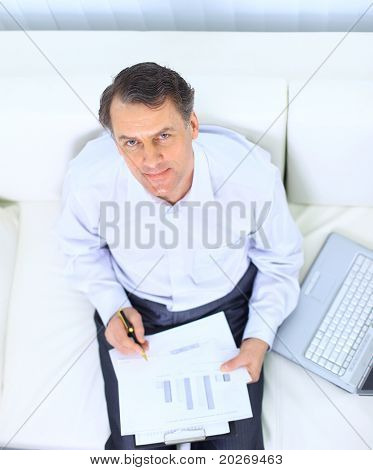 Senior businessman sitting on sofa and using laptop