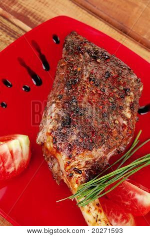savory plate : roasted meat shoulder on red plate with chives and tomato over wooden table