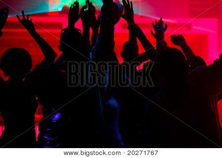 Silhouettes of dancing people having a celebration in a disco club, the light show is sending laser beams through the backlit scene