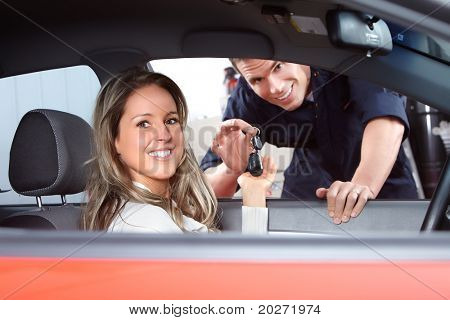 Mechanic handing woman automobile keys. Auto repair