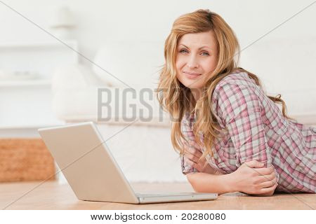 Attractive woman looking at the camera while chatting on her laptop lying on the floor