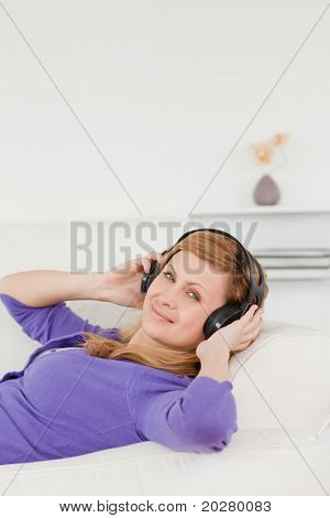 Smiling red-haired woman listening to music and enjoying the moment while lying on a sofa in the living room