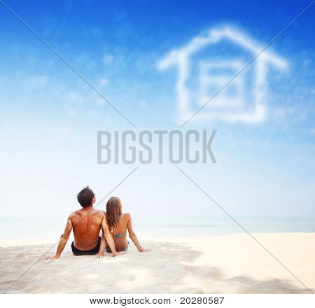 Young family sitting on warm sand by a sea and looking to a blue sky with house shaped clouds