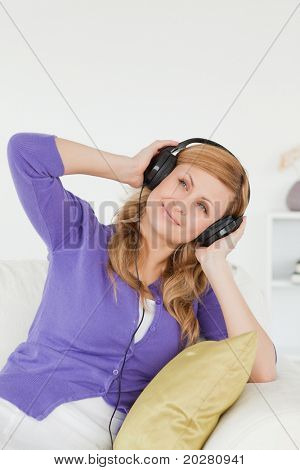 Portrait of a beautiful red-haired woman listening to music and enjoying the moment while sitting on a sofa in the living room