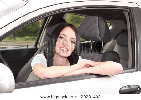 young brunette woman with keys to new car