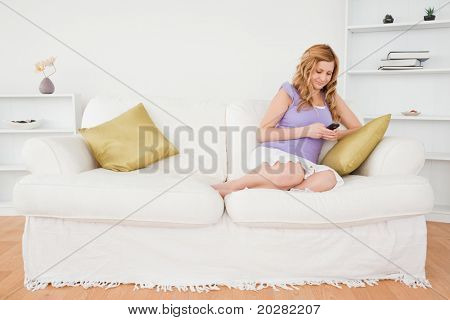 Beautiful red-haired woman writing a text message while sitting on a sofa in the living room