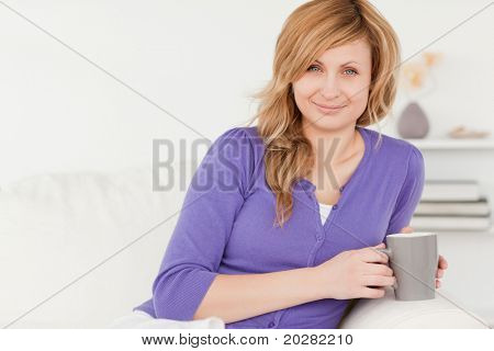 Beautiful red-haired woman holding a cup of coffee while sitting on a sofa in the living room