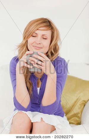 Beautiful red-haired woman holding and smelling a cup of coffee while sitting on a sofa in the living room