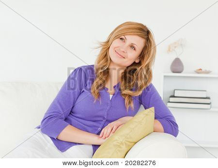 Pretty red-haired woman with a malicious look posing while sitting on a sofa in the living room