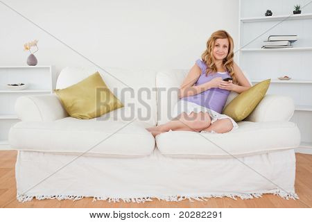 Beautiful red-haired woman writing a text message and posing while sitting on a sofa in the living room