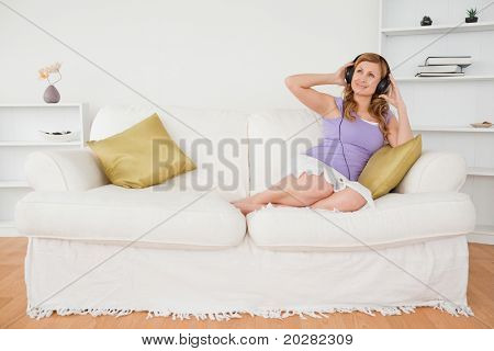 Good looking red-haired woman listening to music and enjoying the moment while sitting on a sofa in the living room