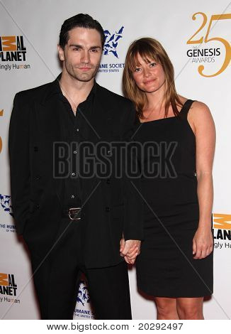 LOS ANGELES - MAR 19:  Sam Witwer & guest arrive to the 25th Annual Genesis Awards  on March 19, 2011 in Century City, CA