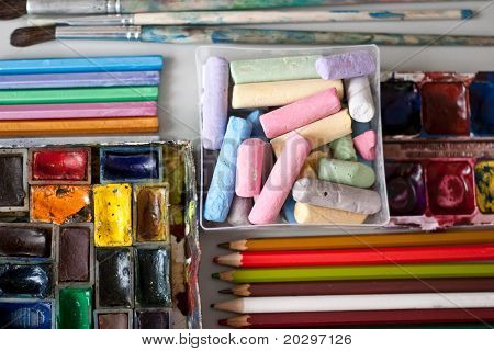 Items for drawing and art: crayons, watercolor paints, brushes, colored pencils.