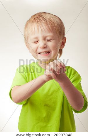 Boy smiled, his eyes shut, hands folded, on a gray background