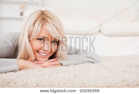 Charming blond woman posing lying down on a carpet in the living room