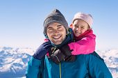 Young daughter riding piggyback on her fathers shoulder. Father and daughter enjoying snow during w poster