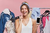 Happy Young Woman Showing Blank Copyspace Display Of Mobile Phone, Holding Hangers Of Stylish Pieces poster