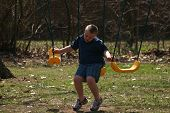 stock photo of swingset  - boy with down syndrome alone on a swingset.