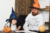 Постер, плакат: Man And Kid With Serious Faces In Witch Hats