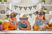Cute little children with carving pumpkin. Happy family preparing for Halloween. Funny kids at home. poster