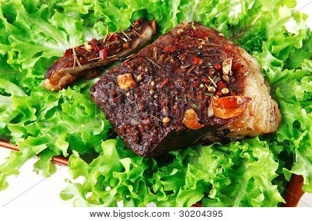 served beef meat on green raw salad close up