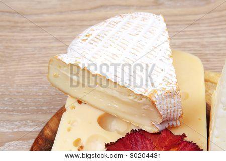 varios tipos de queso en bandeja de madera sobre mesa de madera