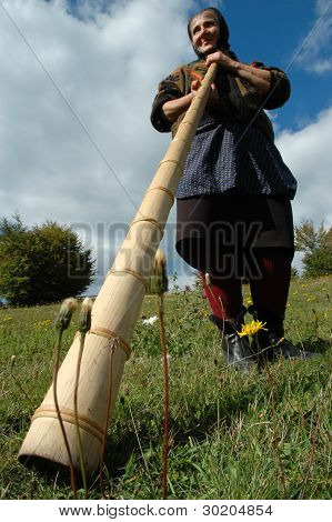 Old woman playing the traditional Romanian alpenhorn
