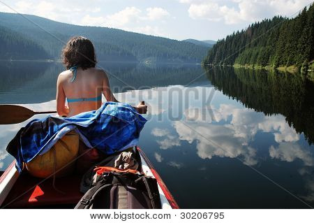 Canoeing girl on a beautiful mountain lake