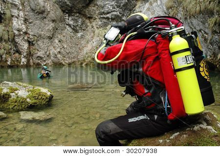 A cave diver emerges from a spring