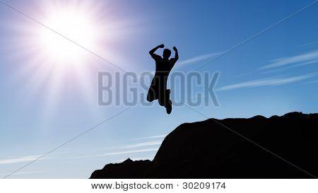 Silhueta do homem pulando de uma rocha