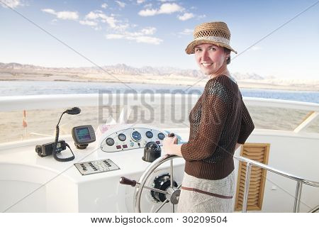 Attractive Young Woman Steering A Boat