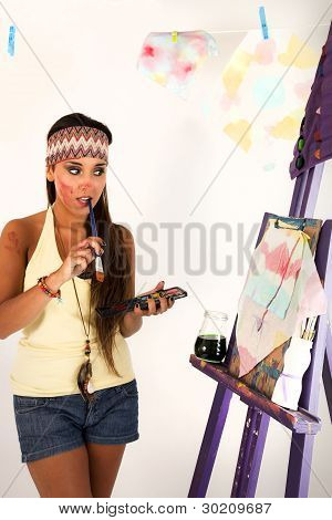 Young woman making a painting, doubting about what to do, with a brush in her mouth