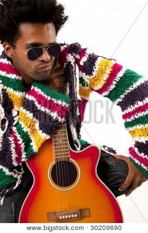 Young and black man, holding an acustic guitar, looking at the right