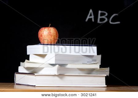 Apple On Stack Of Books In Classroom