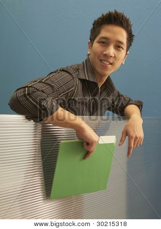 Businessman leaning over cubicle wall