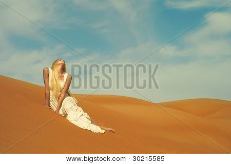 Beautiful blonde in white dress in orange desert. UAE