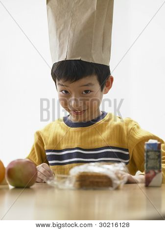 Young boy wearing lunch bag on his head