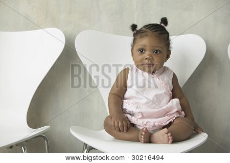 Portrait of baby girl sitting in chair